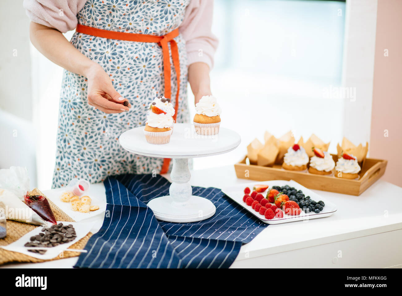 Female baker decorating creamy cupcakes with chocolate topping, a lot of cupcakes lying on wooden tray - Stock Image