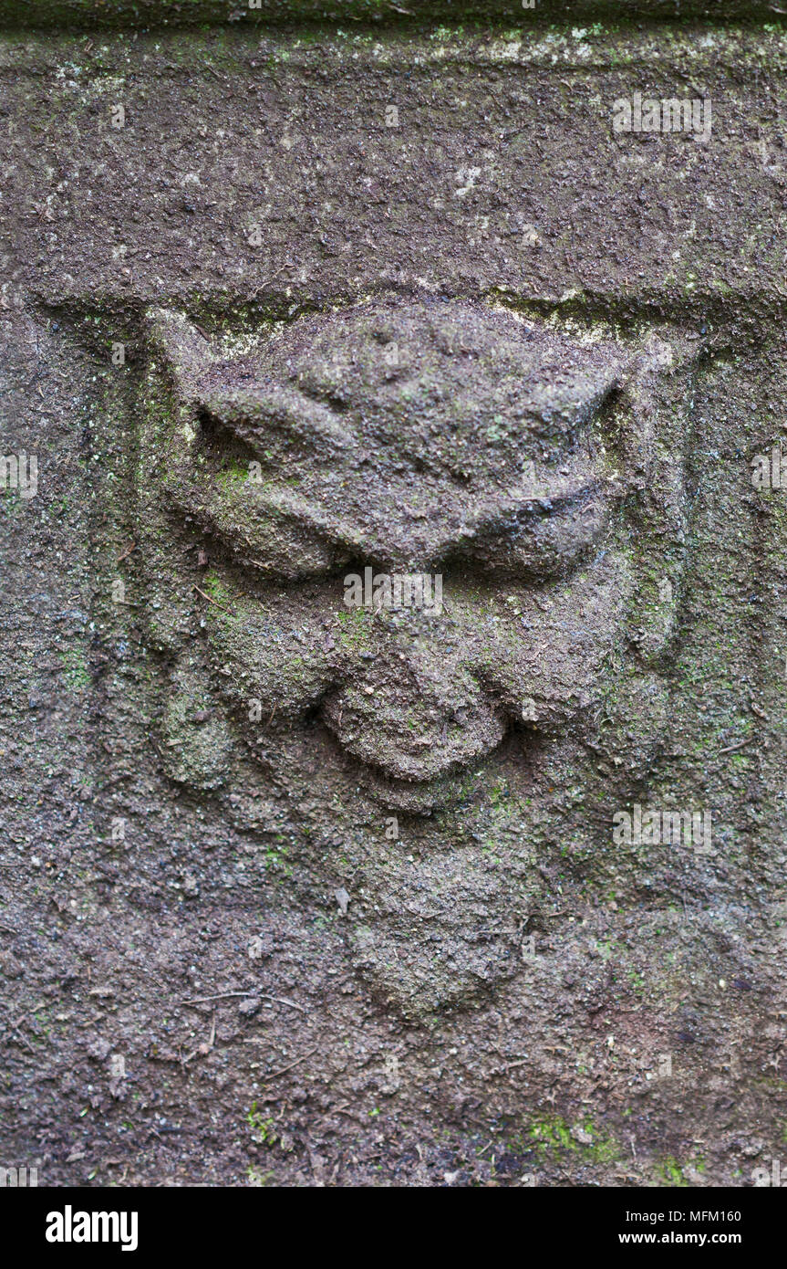 Green Man in stone on ancient pedestal - Stock Image