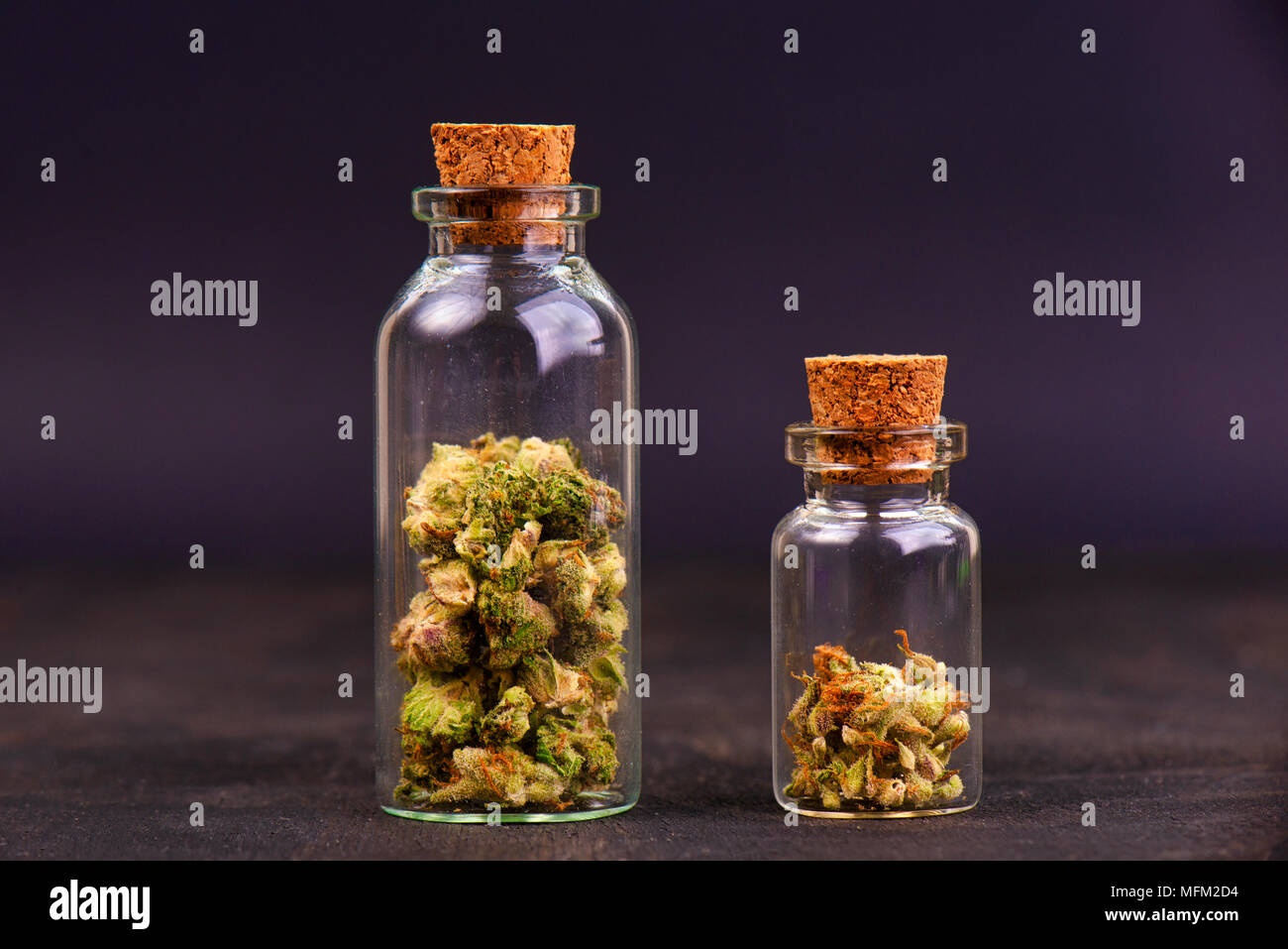 Detail of assorted jars with cannabis calyxes (sour tangie strain) isolated on black background - Medical marijuana dispensary concept Stock Photo