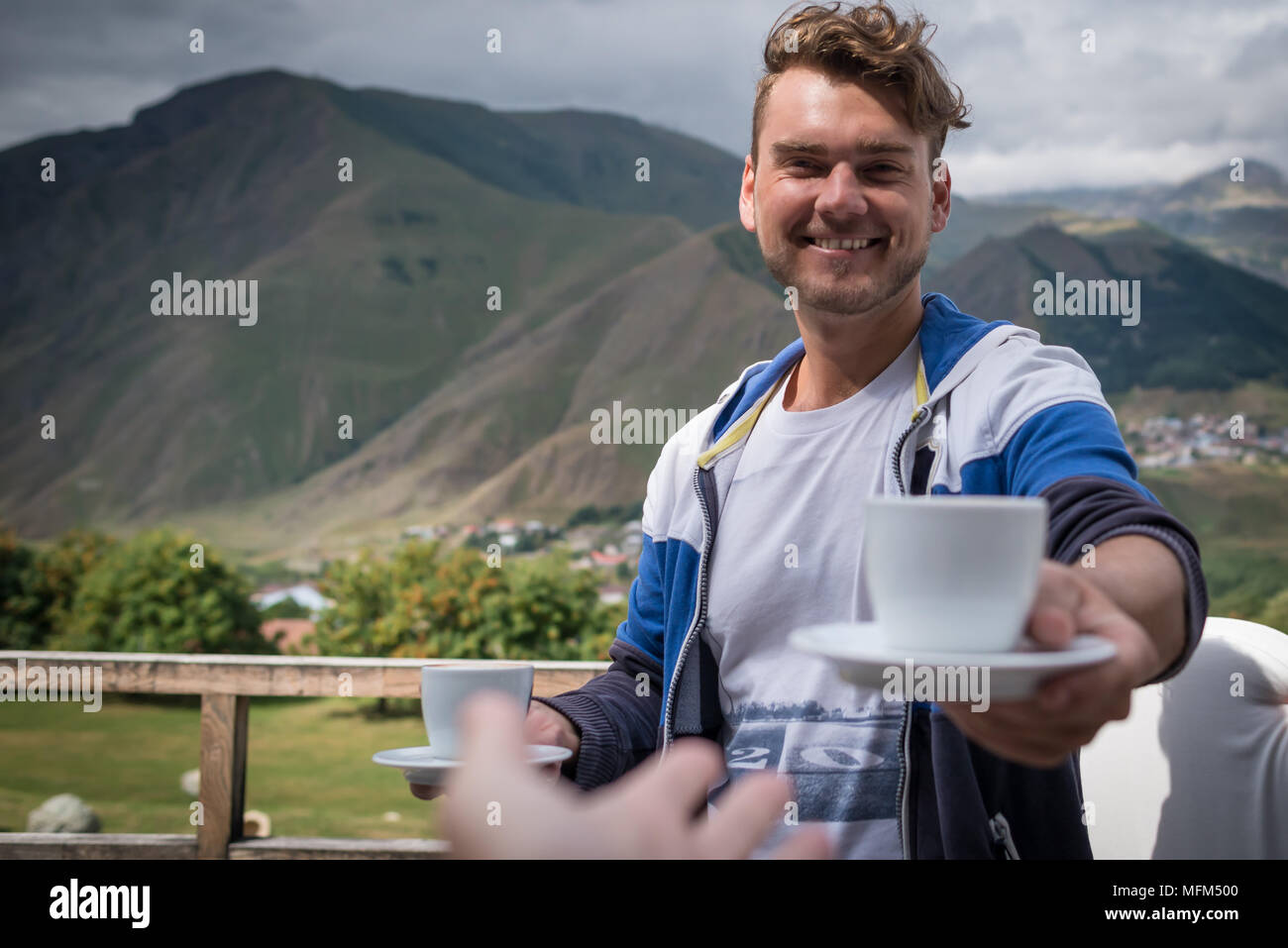Young man holds out a cup of coffee. Happy guy with drinks in the morning on the terrace with beautiful view on mountains. Good morning concept. - Stock Image