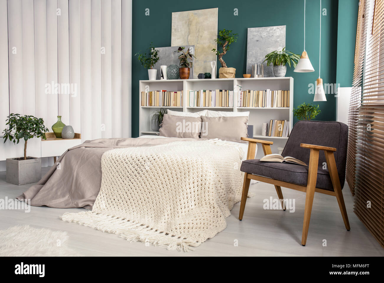White and green bedroom interior with a knit blanket on beige bed ...
