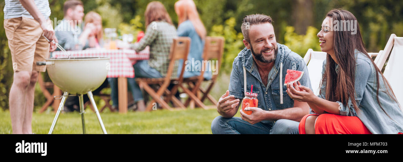 Smiling woman eating watermelon and her  friend drinking juice during garden party - Stock Image