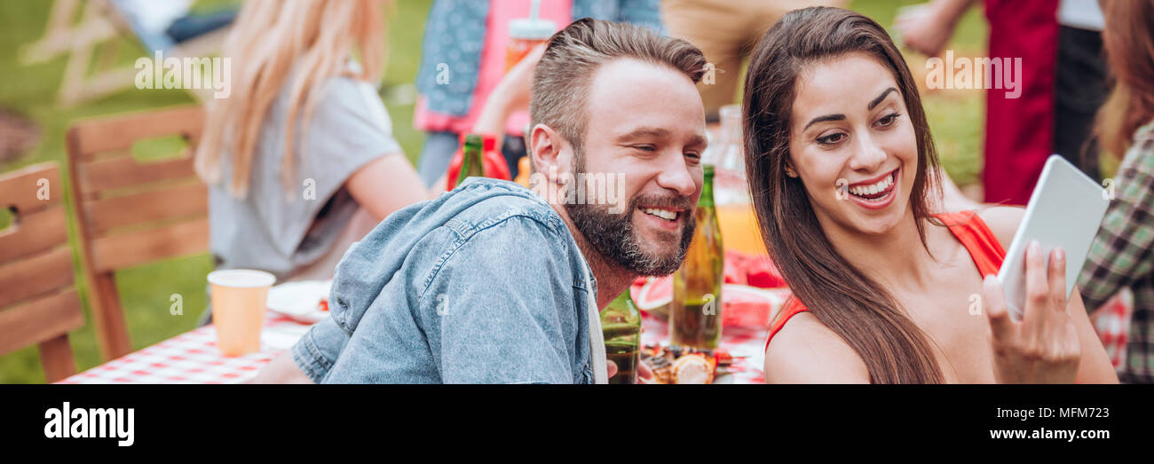 Panorama of happy woman taking a selfie with her friend during a garden party - Stock Image
