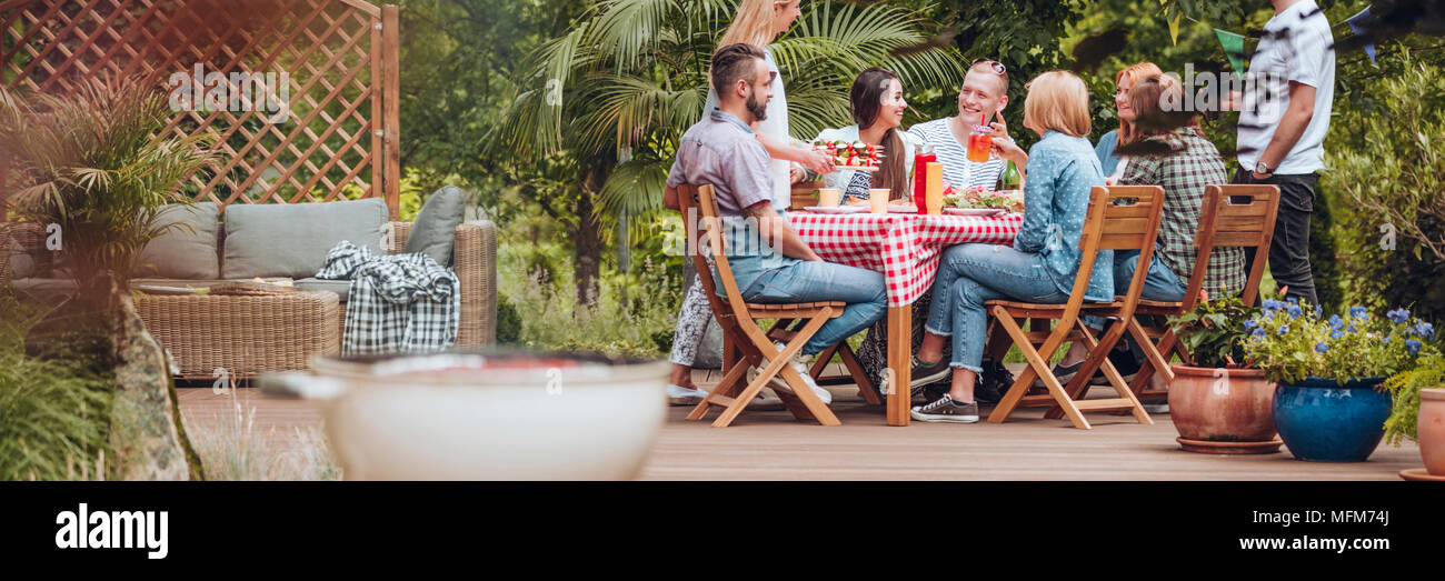 Group of friends eating grilled food during meeting in the yard - Stock Image