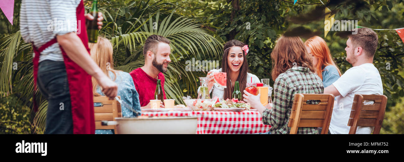 Panorama of smiling friends enjoying a birthday party in the garden Stock Photo