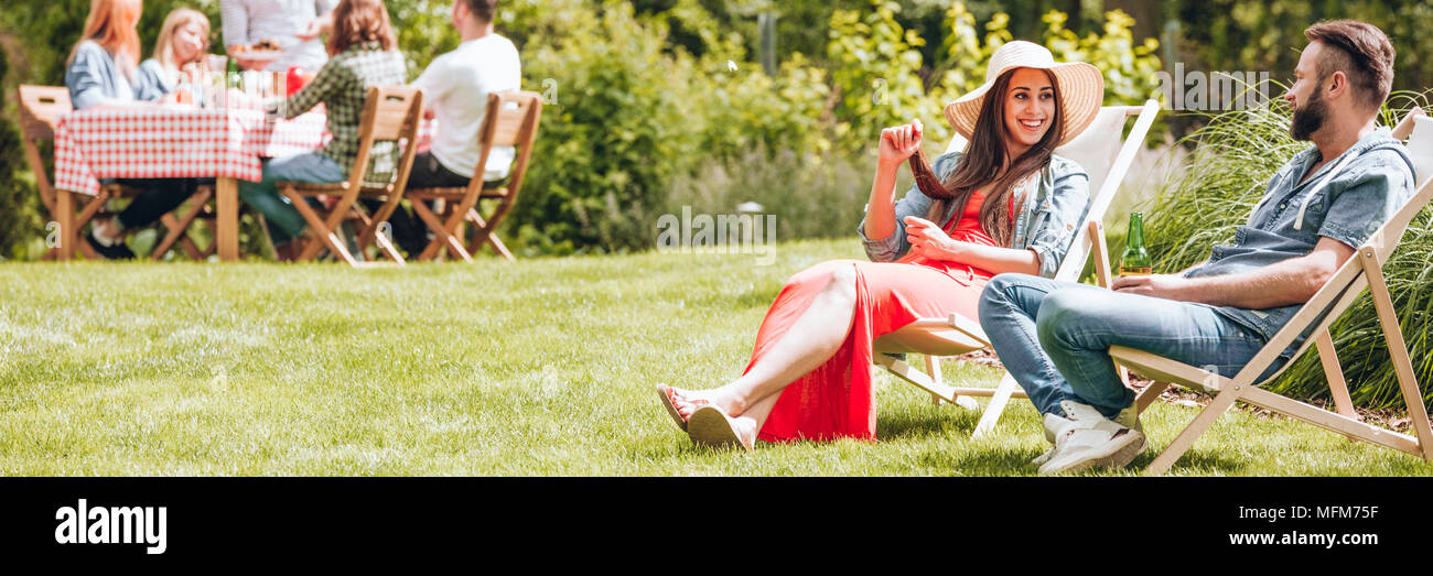 Happy woman relaxing with a friend on sunbeds during sunny day in the summer - Stock Image