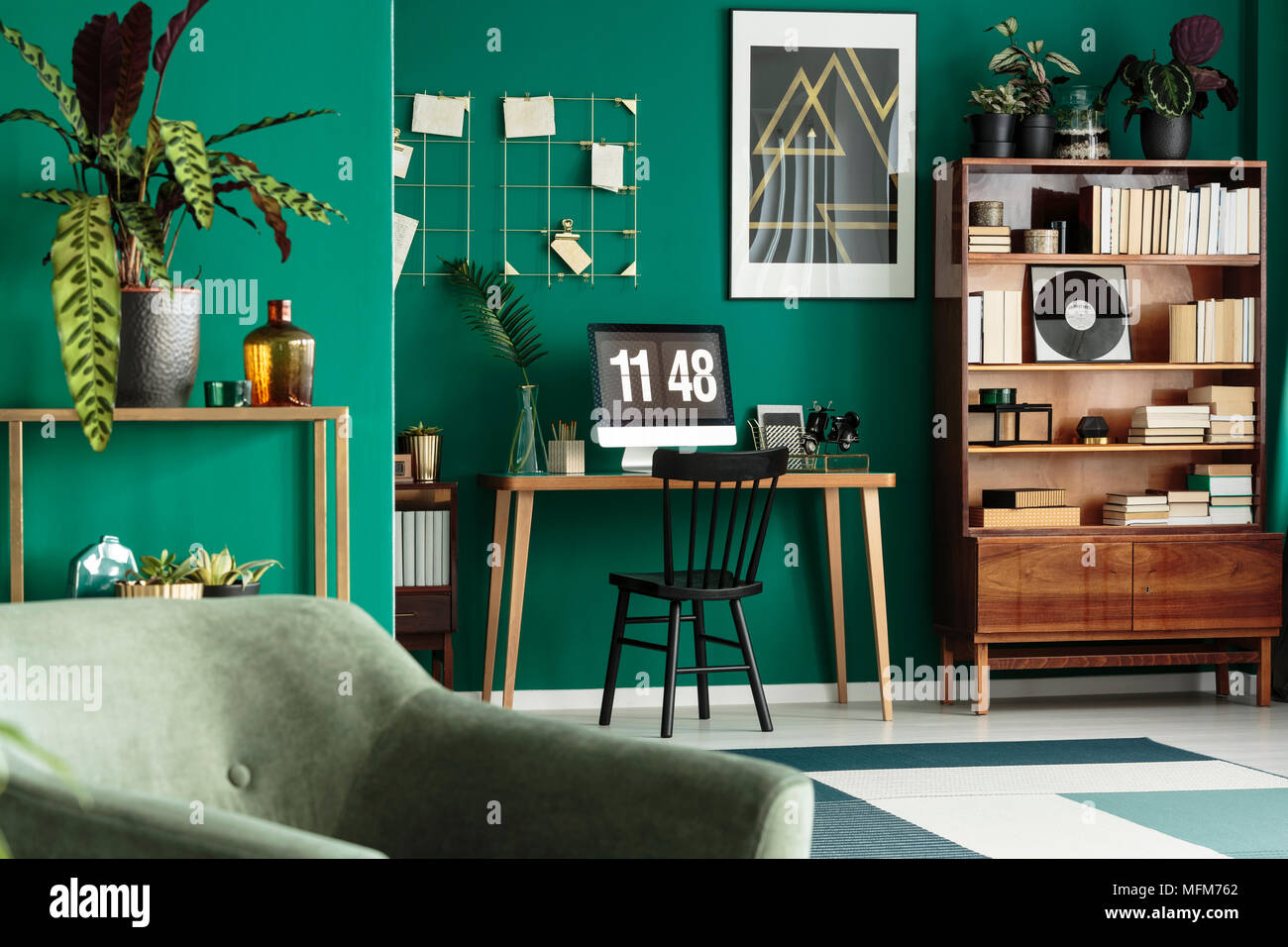 Hipster Home Office Desk With Desktop Computer And An Antique, Wooden  Bookcase In A Green, Designer Living Room Interior With Plants