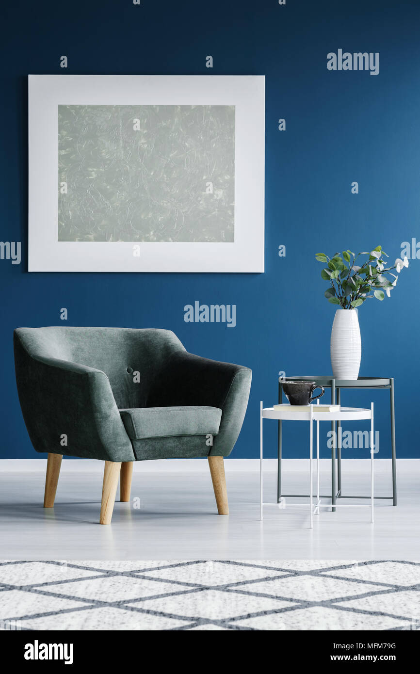 Grey, comfy armchair, flower on a table and painting on the blue wall in living room interior - Stock Image