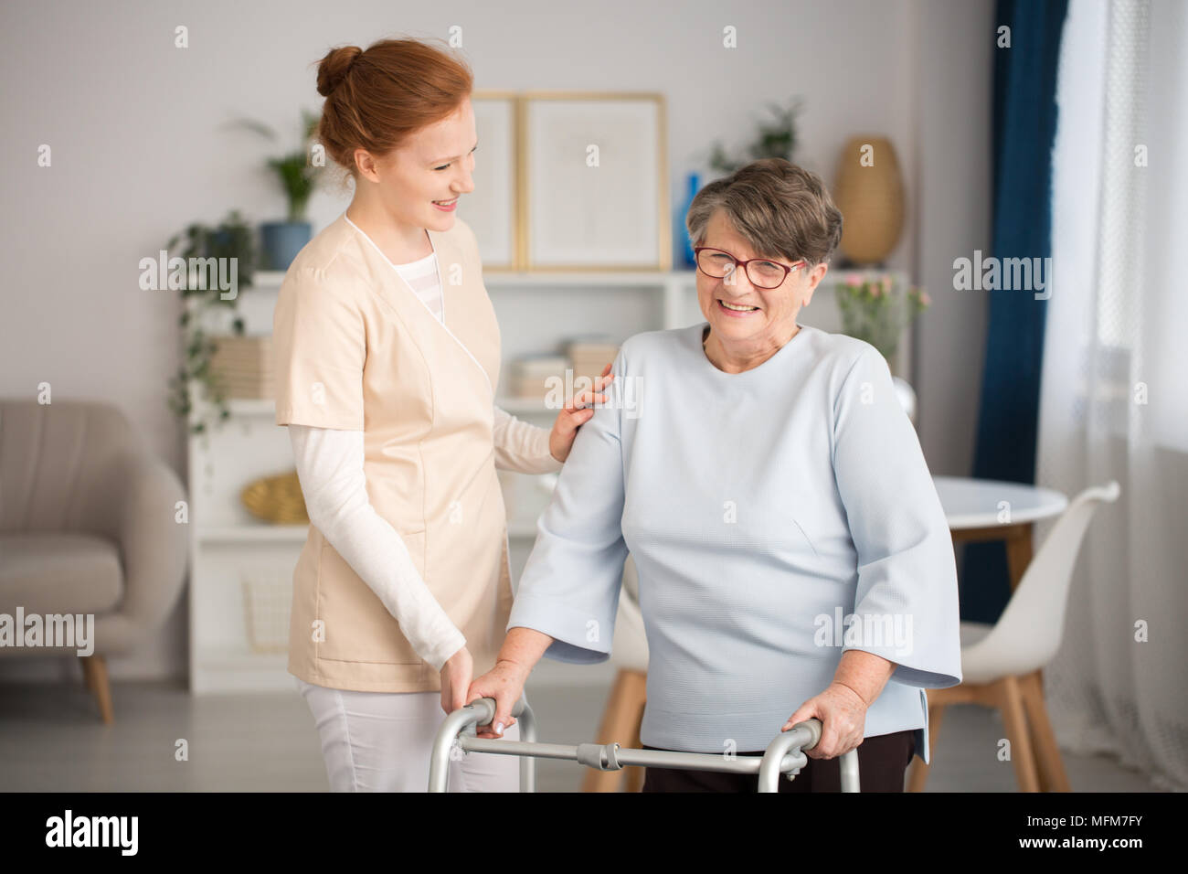 Professional medical caretaker in uniform helping smiling senior woman with a walker in a living room of private luxury healthcare clinic - Stock Image