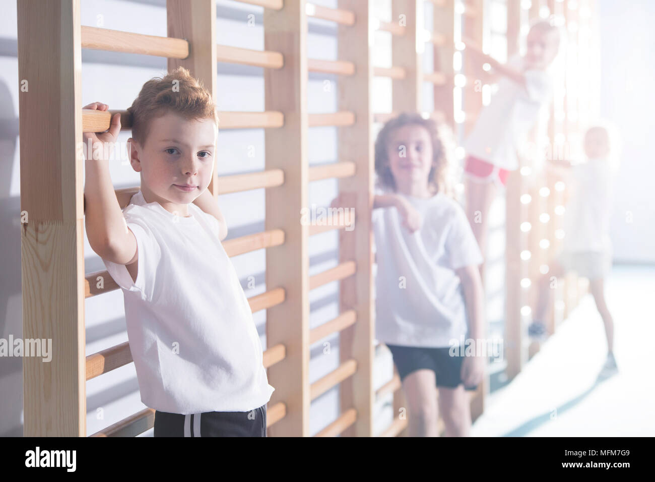 Young kids working out with wall bars at a school gym - Stock Image