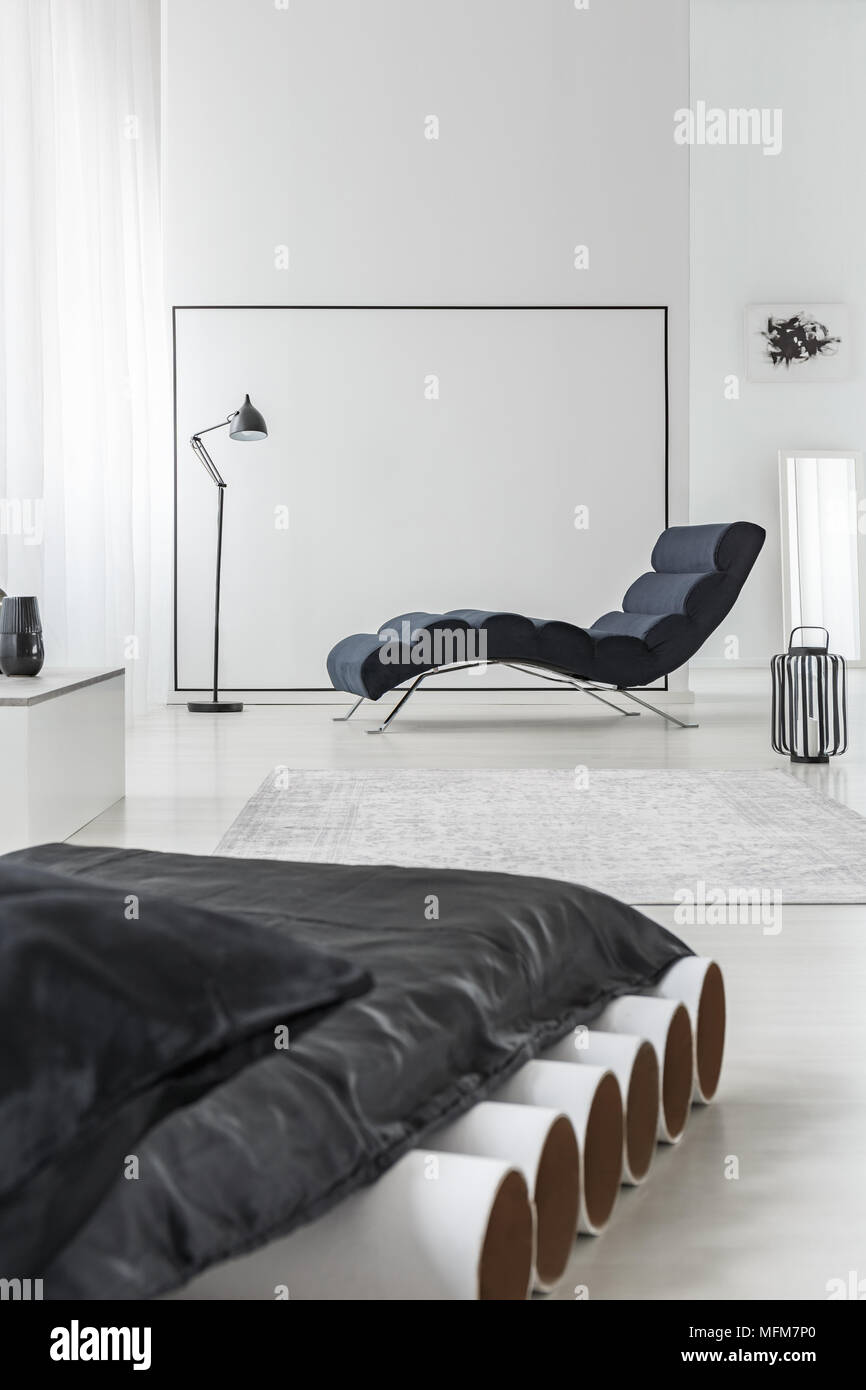 Black mattress on white tubes in bedroom interior with chaise lounge ...
