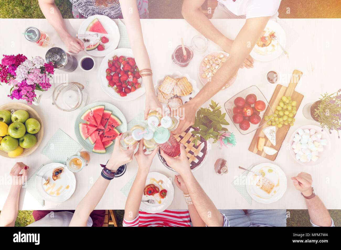 Mixed-race group eating healthy food outdoors and toasting - Stock Image