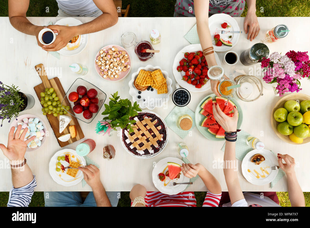 Students eating a healthy meal outdoors on a white table and having a good time - Stock Image