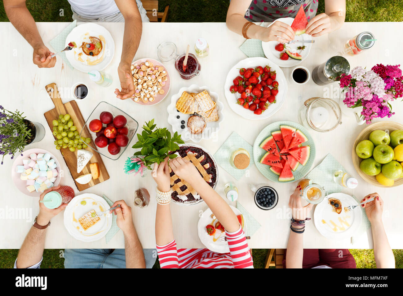 Young people sharing food in the garden eating fruit, pie, cheese with flowers and candle on the table - Stock Image