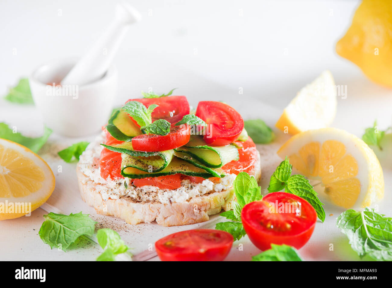 Crisp bread healthy snack with salmon, cottage cheese, cucumber stripes, fresh cherry tomatoes, mint, lemon juice, pepper. Easy breakfast close-up on  - Stock Image