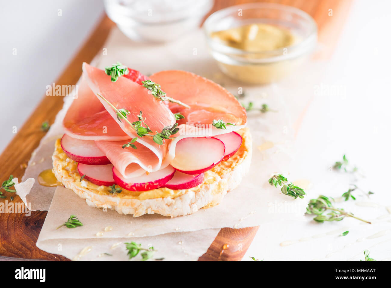 Crisp bread healthy snack with Parma ham, radish slices, mustard, sea salt, honey and fresh thyme. Easy breakfast close-up on a white background with  - Stock Image