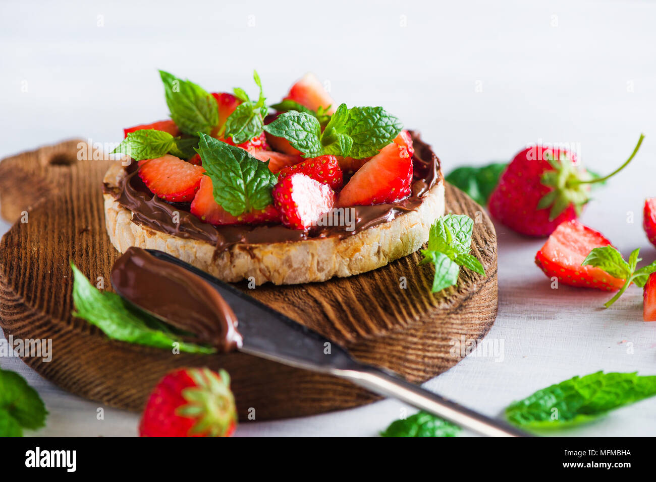 Crisp bread healthy snack with fresh strawberries, chocolate spread, mint leaves on a round cutting board with a dessert knife. Easy breakfast close-u Stock Photo
