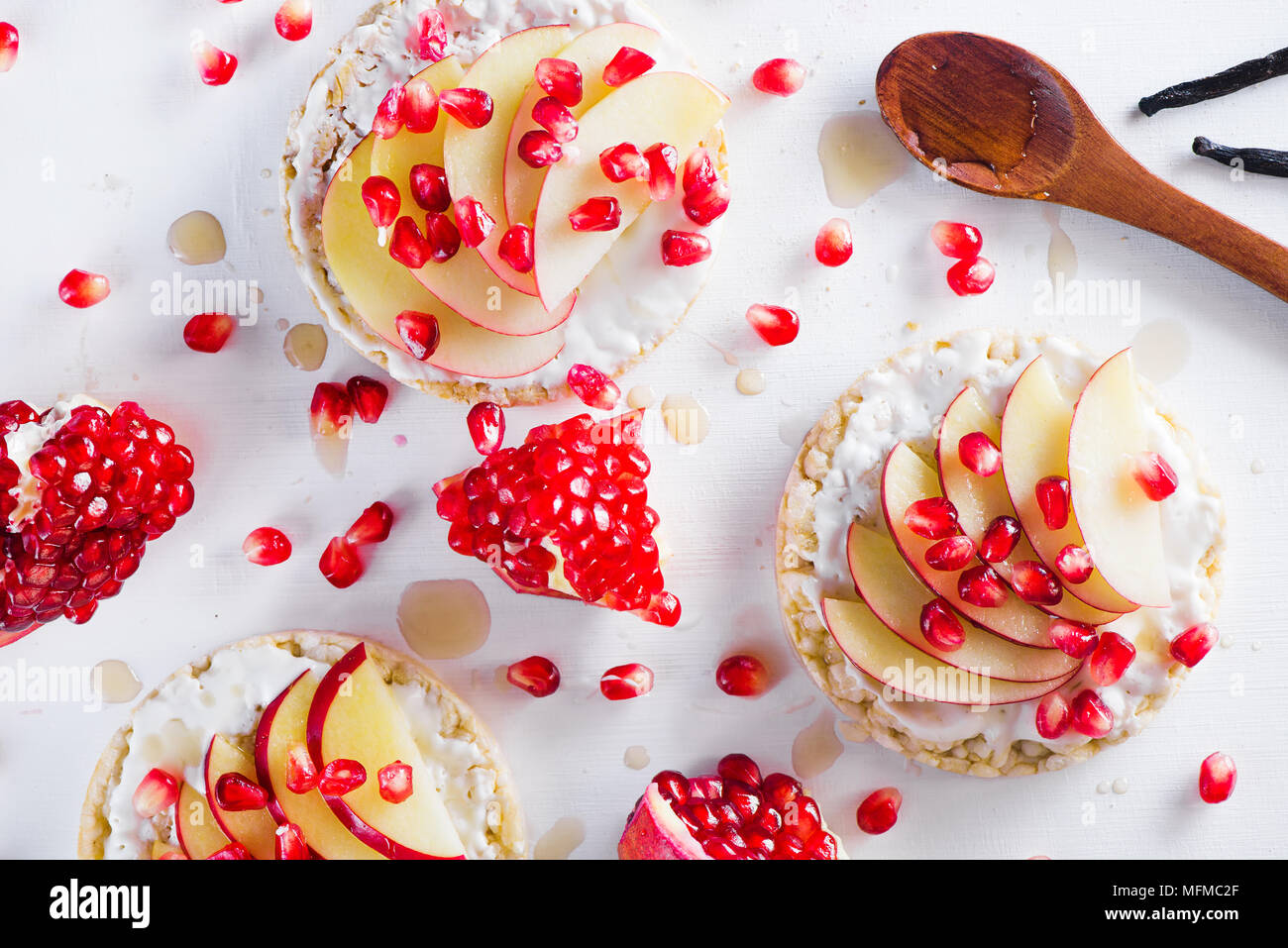 Crisp bread healthy snack with apple slices, soft cottage cheese, vanilla, honey, pomegranate seeds. Easy breakfast concept on a white background with - Stock Image