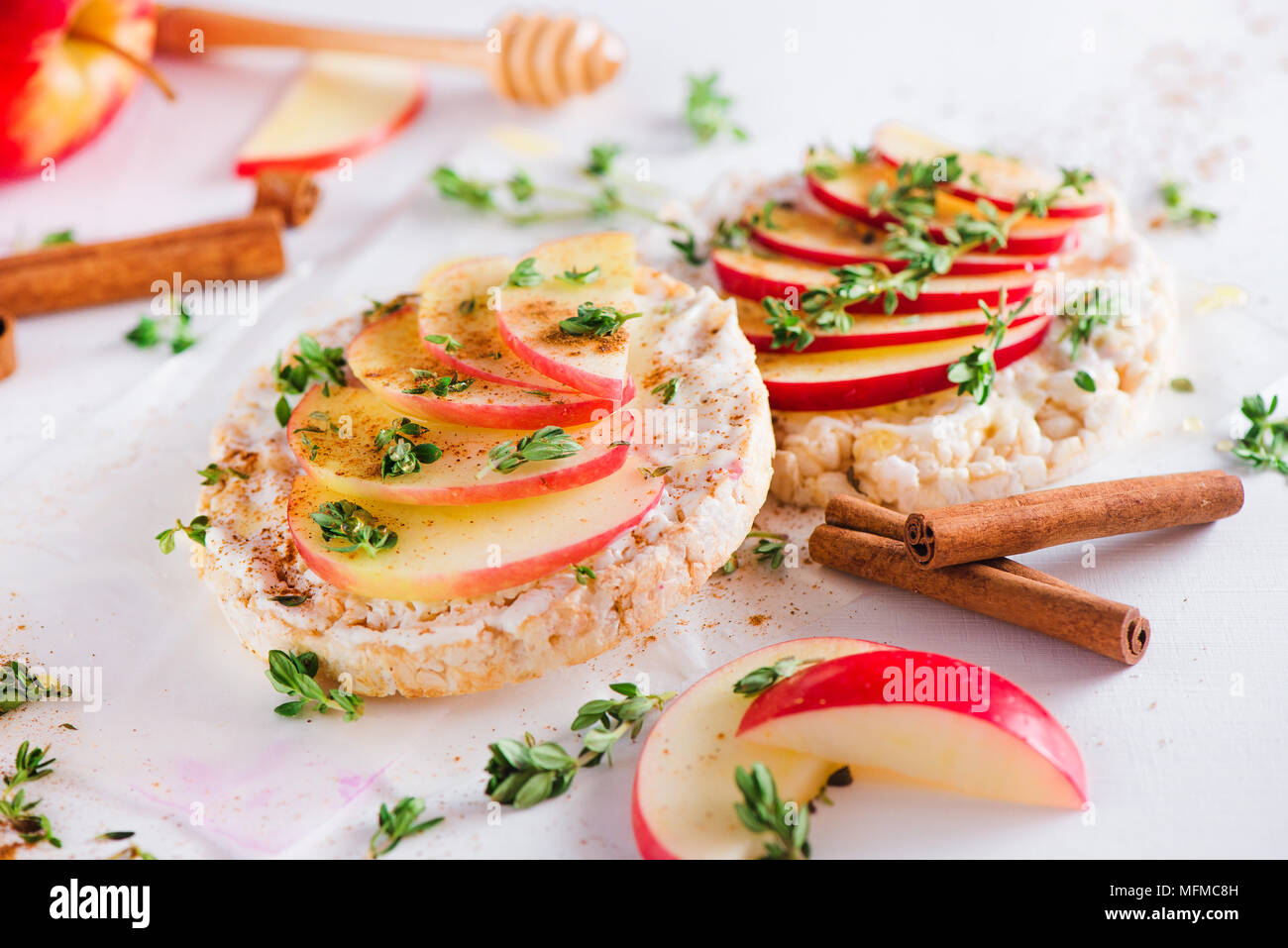 Crisp bread snack with apple slices, cinnamon, greek youghurt, honey and fresh thyme. Easy breakfast close-up on a white background with copy space. - Stock Image