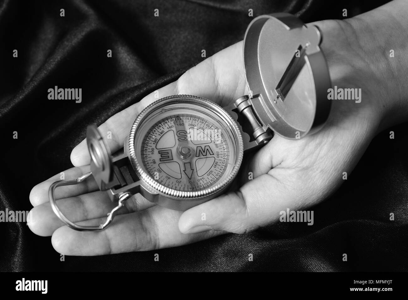 A magnetic compass in the palm of a hand. - Stock Image
