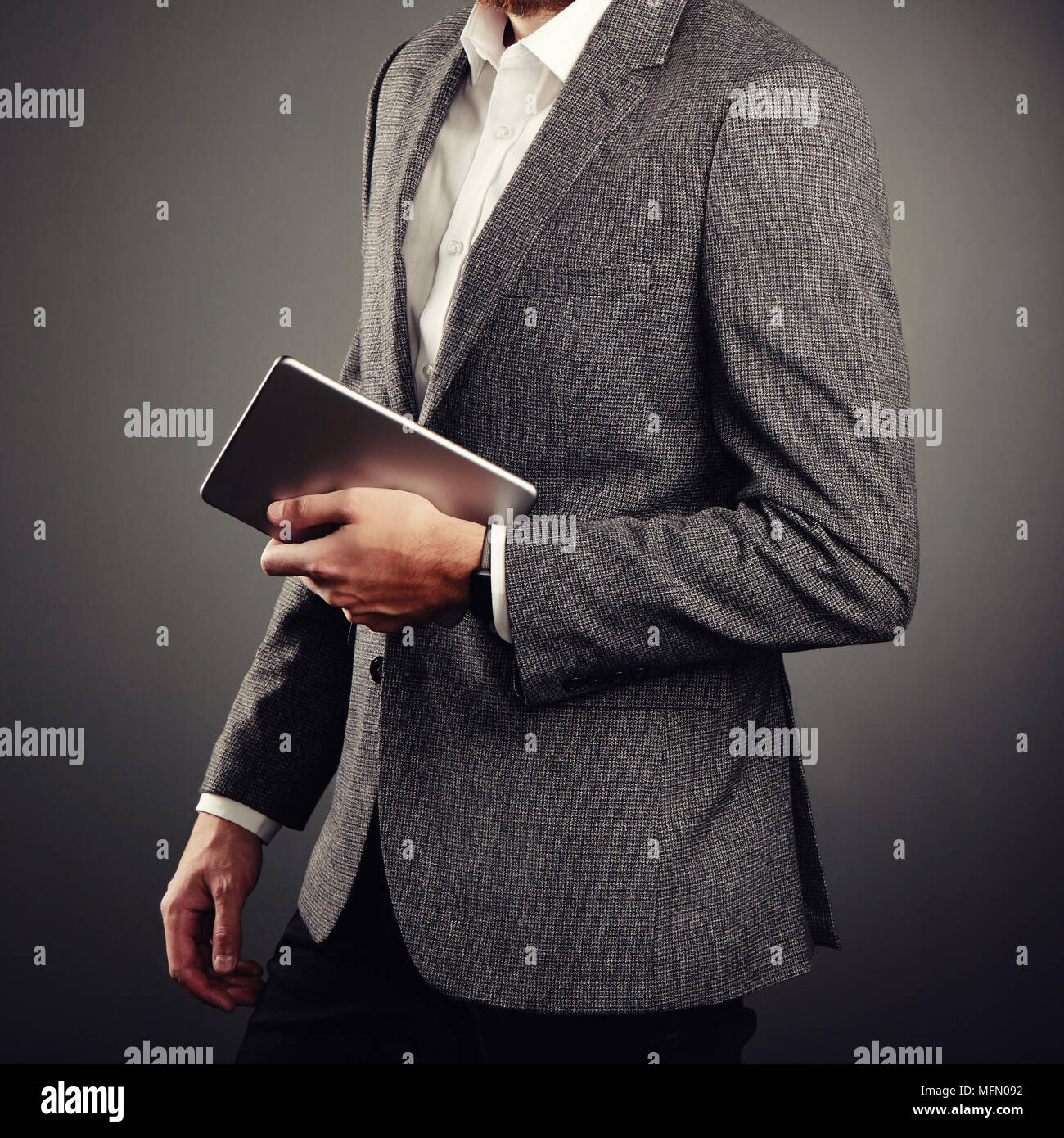 Handsome Young Man in Business Suit. Casual style and Electronic Gadgets. Smart Watches and Digital Tablet - Stock Image