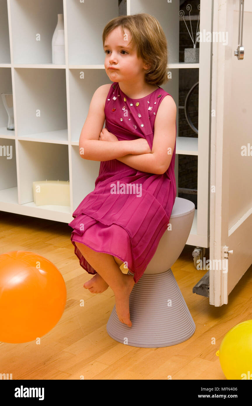 Girl sitting on a stool and looking away   Ref:   Compulsory Credit: - Stock Image