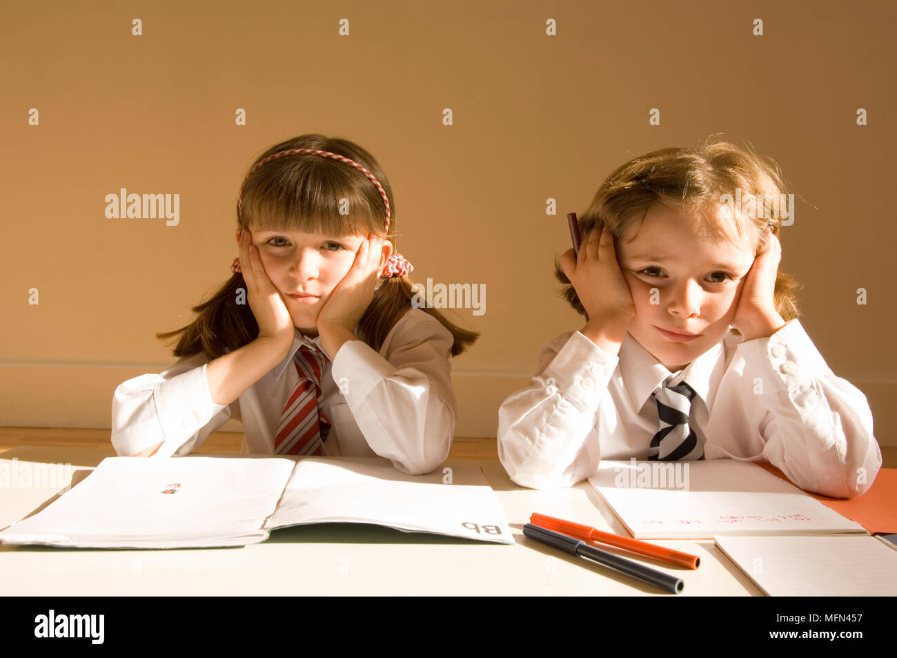 Portrait of two girls sitting at a table with their head in their hands   Ref:   Compulsory Credit: Stock Photo