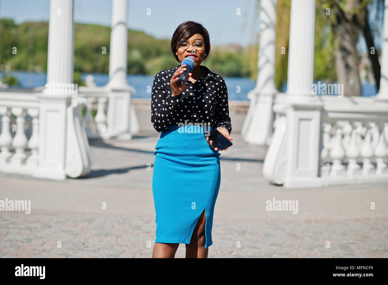 Stylish African American Model Girl Tv Presenter With Microphone In Glasses Blue Skirt And Black Blouse Posed Outdoor Against White Stone Arch With M
