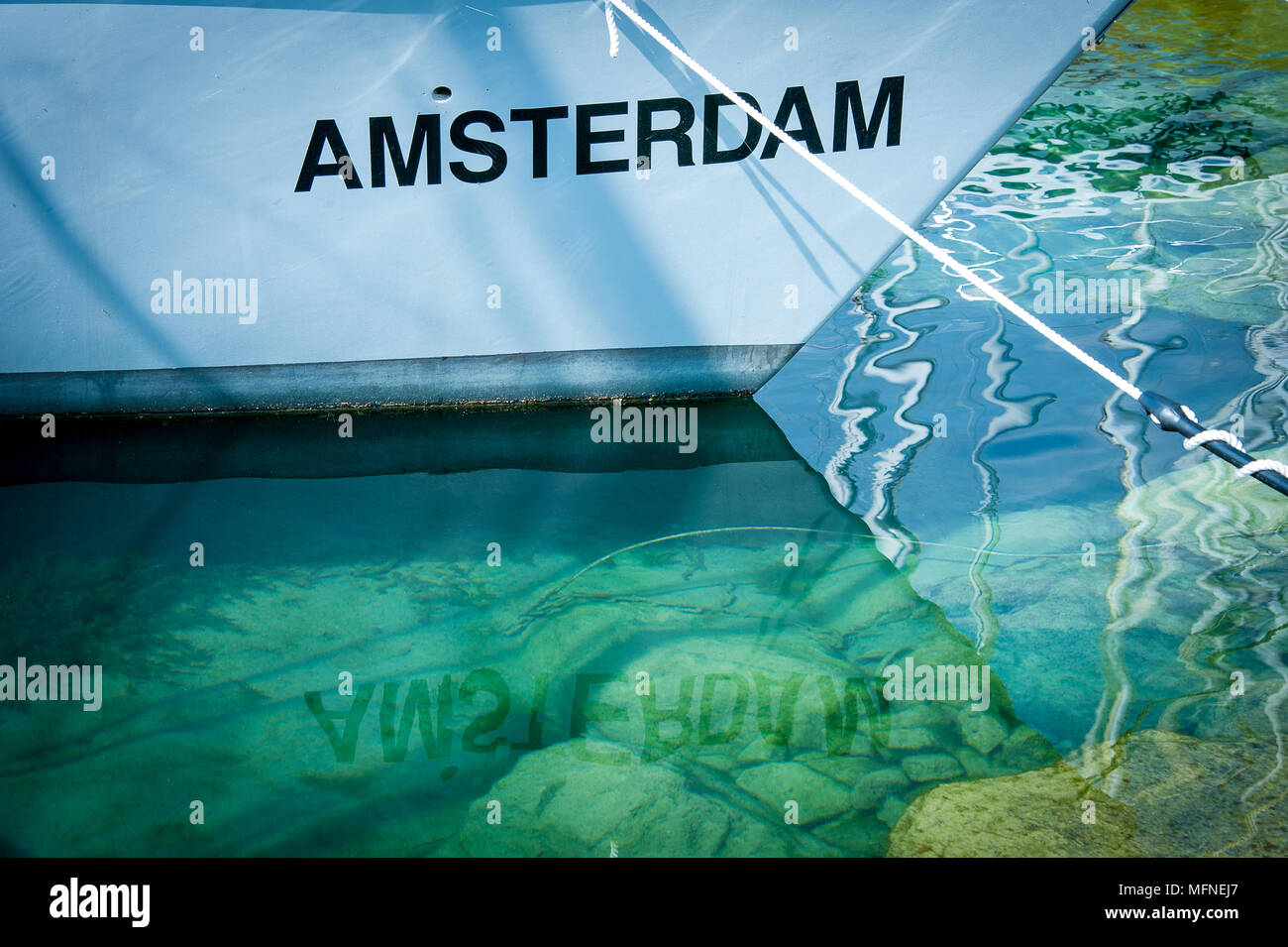 A white boat moored in a turquoise lake. Nice geometric lines and rippled reflections of the name Amsterdam - Stock Image