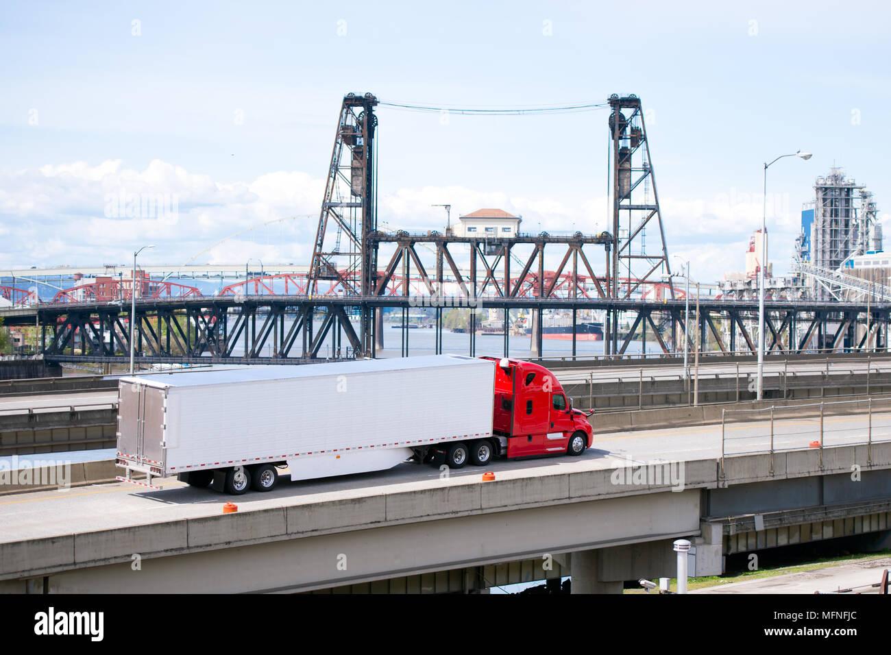 Big rig bright red semi truck transporting semi trailer with