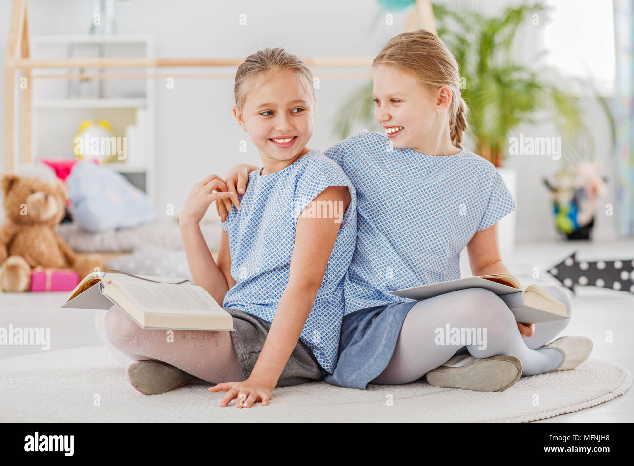 Girl laughing with an arm around her sister's shoulder, sitting on a white rug and reading together - Stock Image
