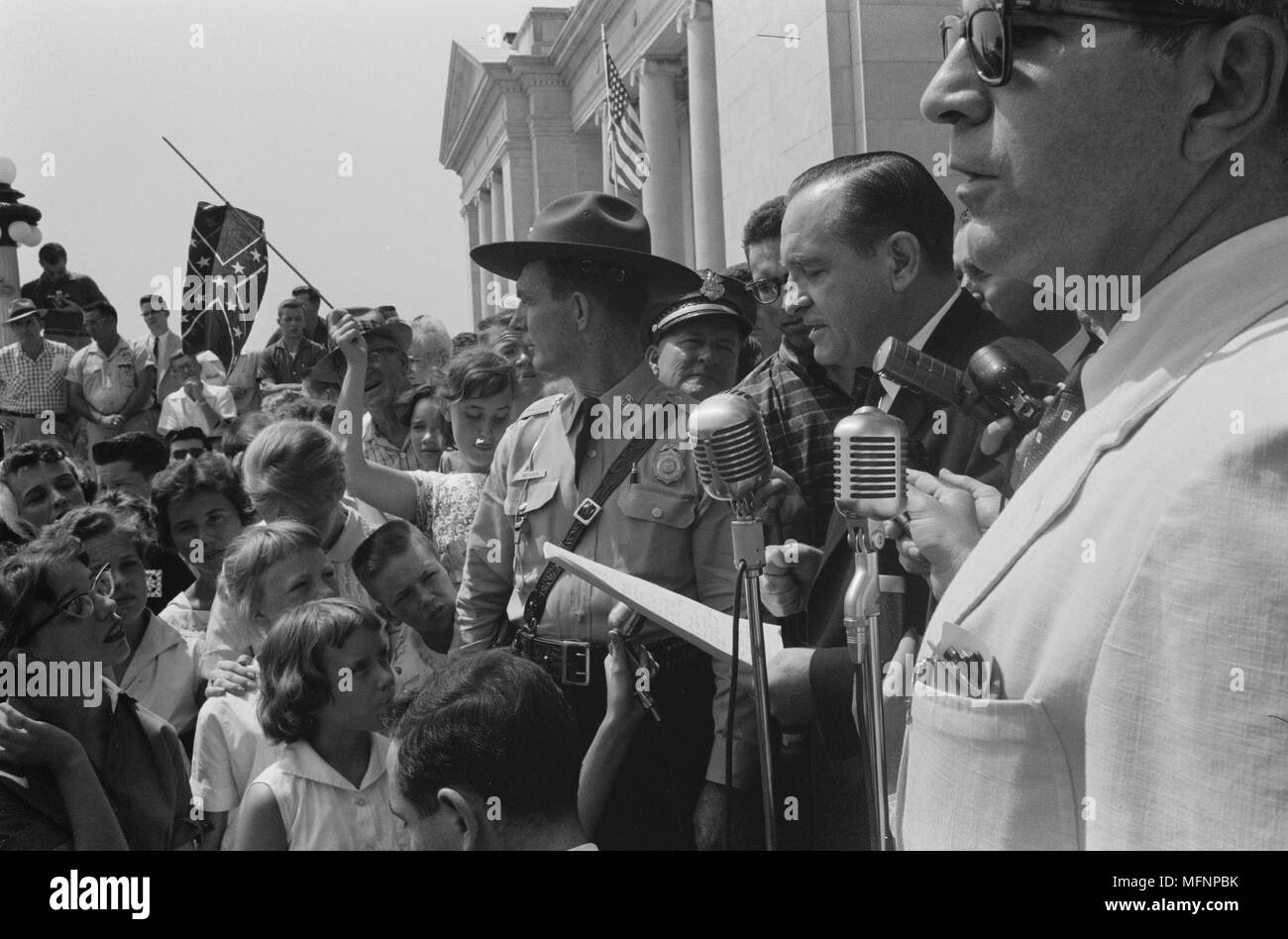 Little Rock, USA, 1959. Rally at state capitol.  Photograph shows a group of people, one holding a Confederate flag, surrounding speakers and National Guard, protesting the admission of the 'Little Rock Nine' to Central High School. 20 August 1959. Photographer: John T  Bledsoe. - Stock Image