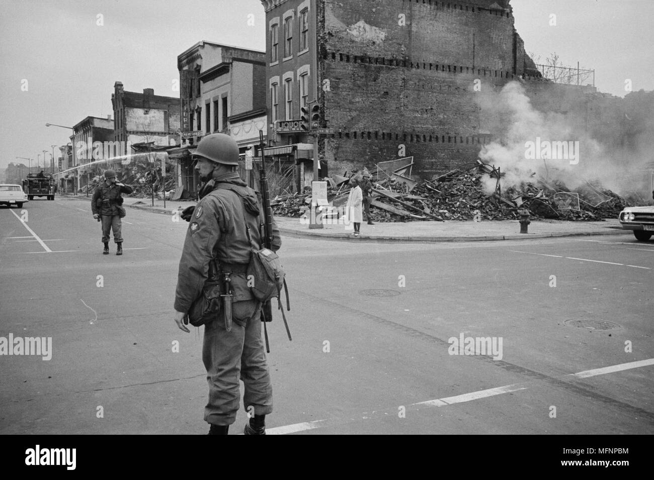Soldier standing guard in a Washington, D.C., street with the ruins of buildings that were destroyed during the riots that followed the assassination of Martin Luther King Jr., 8 April 1968. Photographer:  Warren K  Leffler. - Stock Image