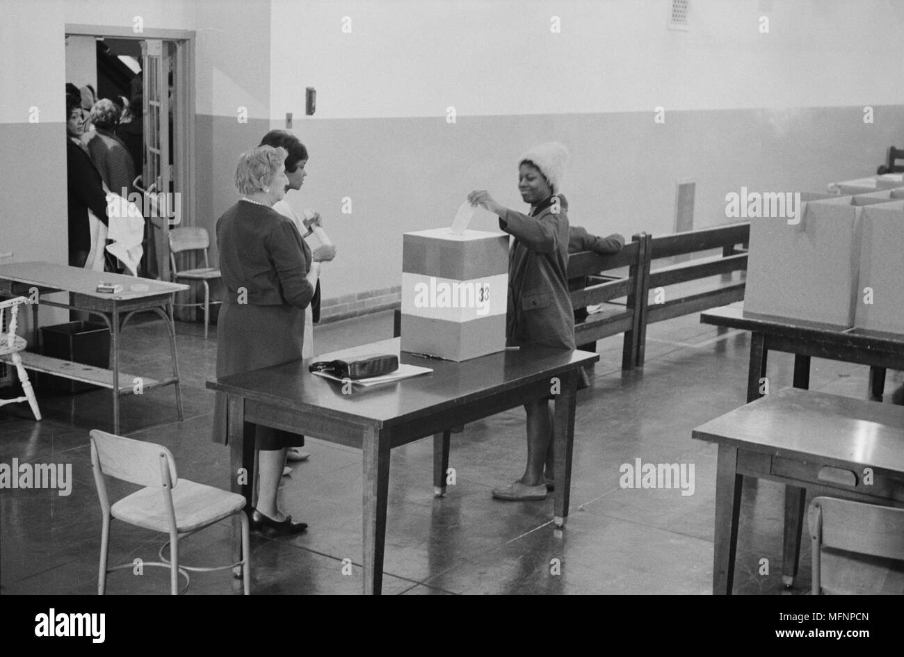 Young African American woman casting her vote in a ballot box at voting station in the Cardoza High School building, Washington. DC, 3 May 1964. Photographer:  Marion S Trikosko. - Stock Image