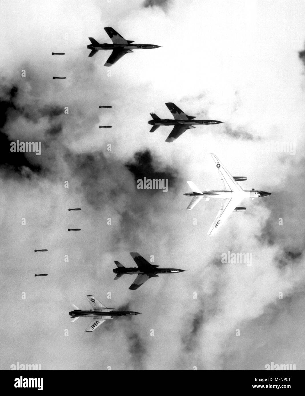 Flying under radar control with a B-66 Destroyer, Air Force F-105 Thunderchief pilots bomb a military target through low clouds over the southern panhandle of North Vietnam, 14 June 1966. - Stock Image