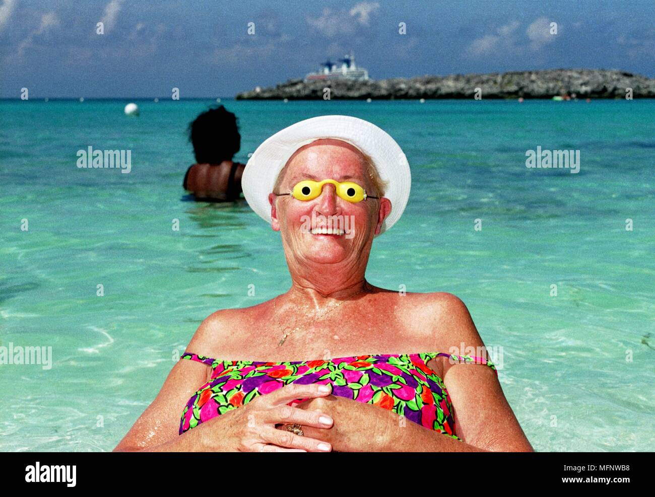 American cruiseship passenger wearing sun goggles on a cruiseline's private beach in The Bahamas.     Ref: CRB459_103533_0009  COMPULSORY CREDIT: Ian - Stock Image