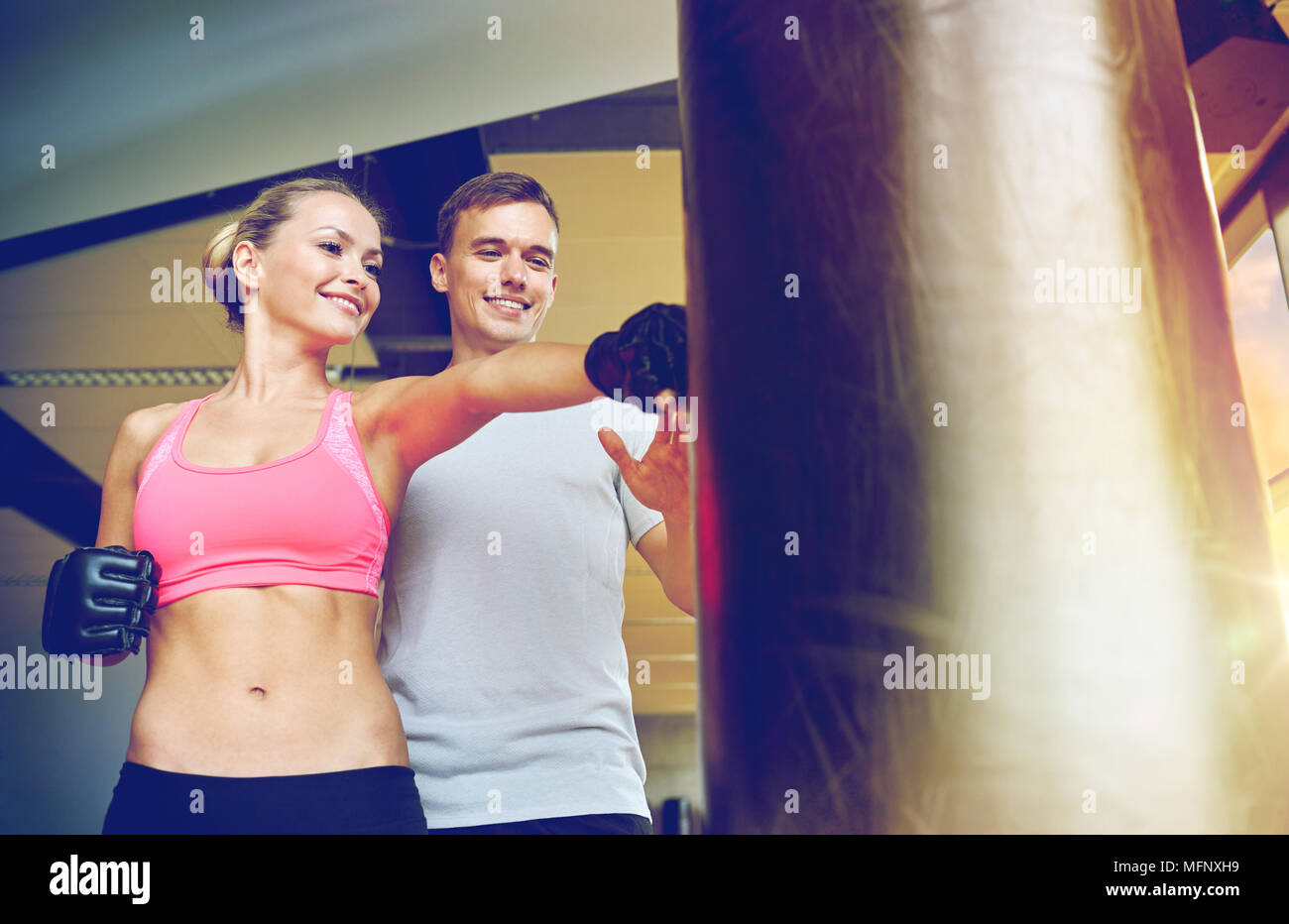 smiling woman with personal trainer boxing in gym - Stock Image