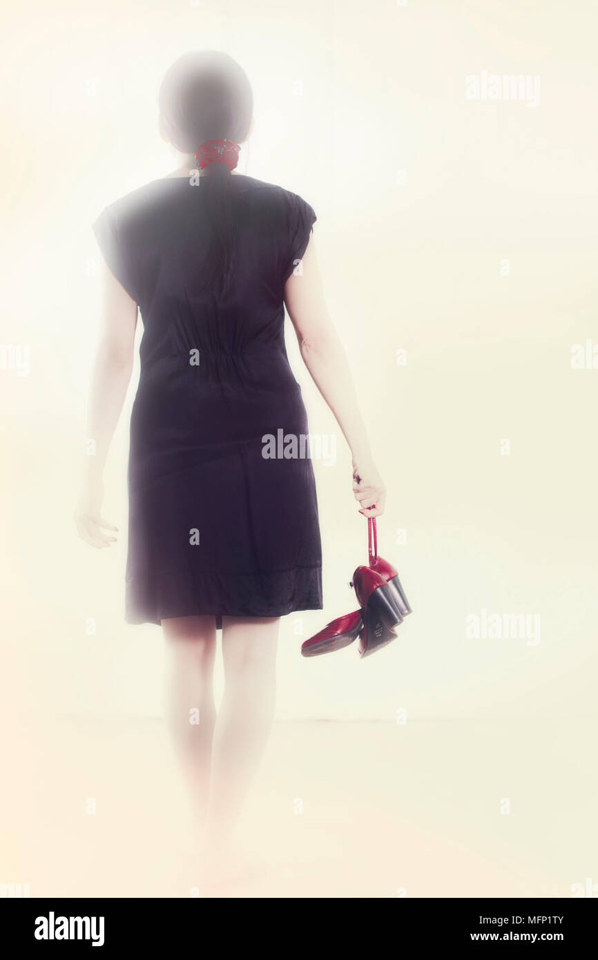 Woman In A Black Dress Goes With Red Shoes In Hand Into The Light