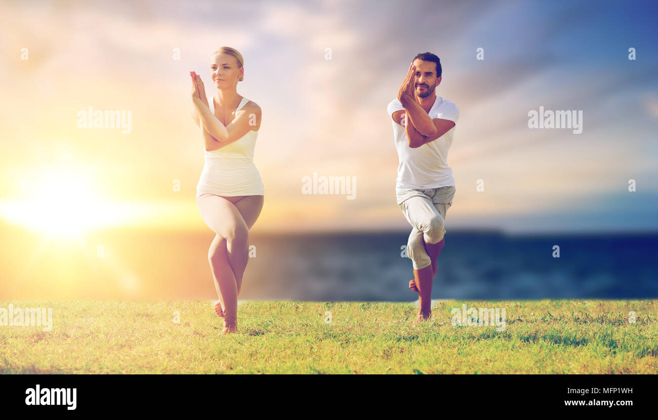 couple making yoga eagle pose outdoors - Stock Image