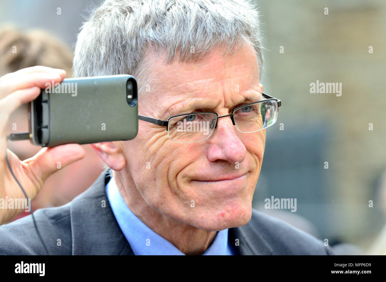 Simon Calder - travel writer and broadcaster - filming an interview on his mobile phone - Stock Image