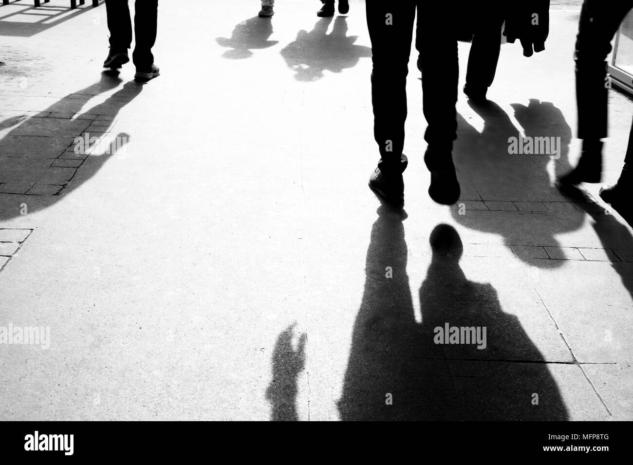 Silhouettes and shadows of people walking on the city sidewalk in early morning black and white - Stock Image