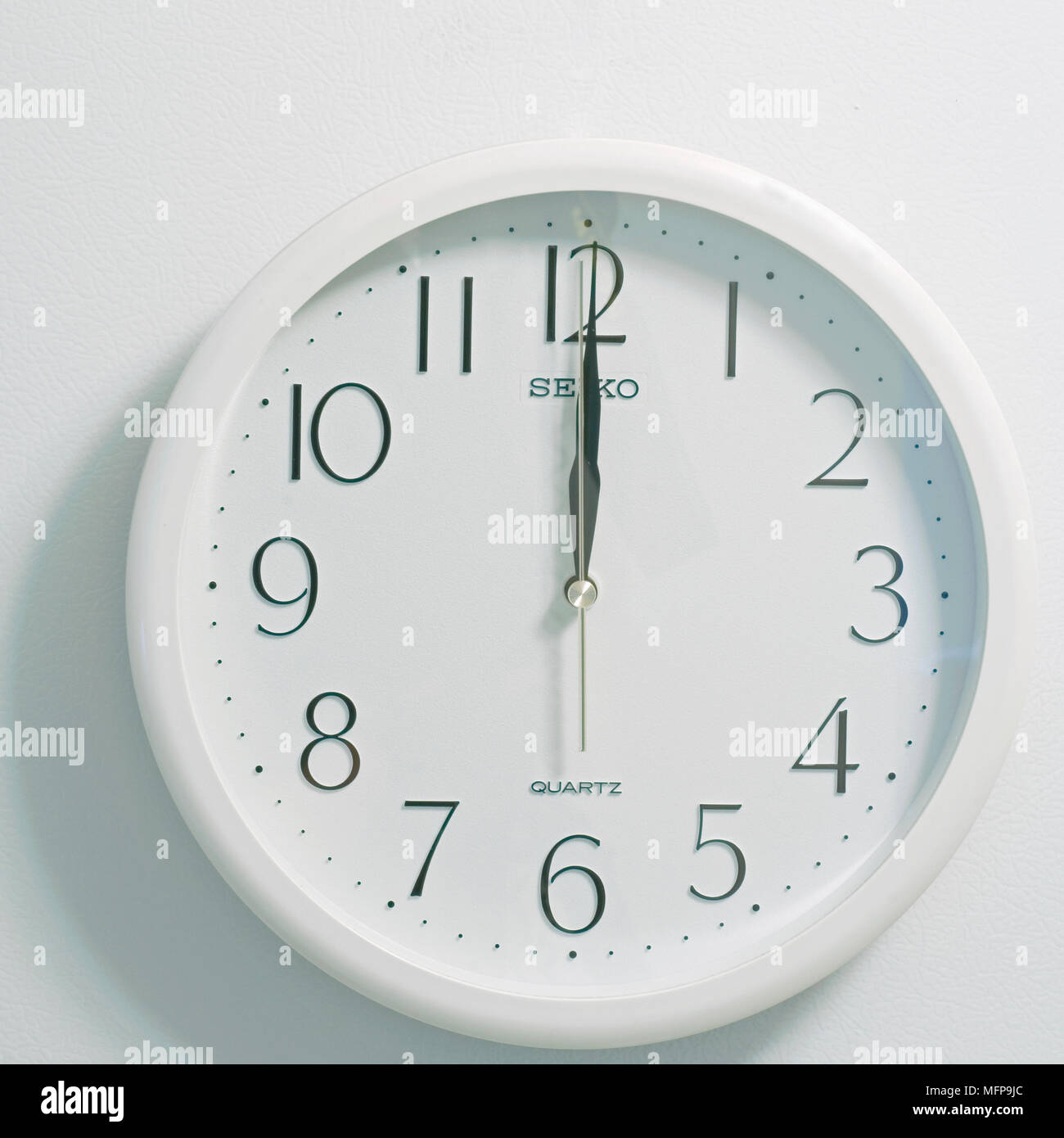 closeup of face of modern clock style showing round white and black dial at the time twelve o'clock noon or midnight on white background - Stock Image