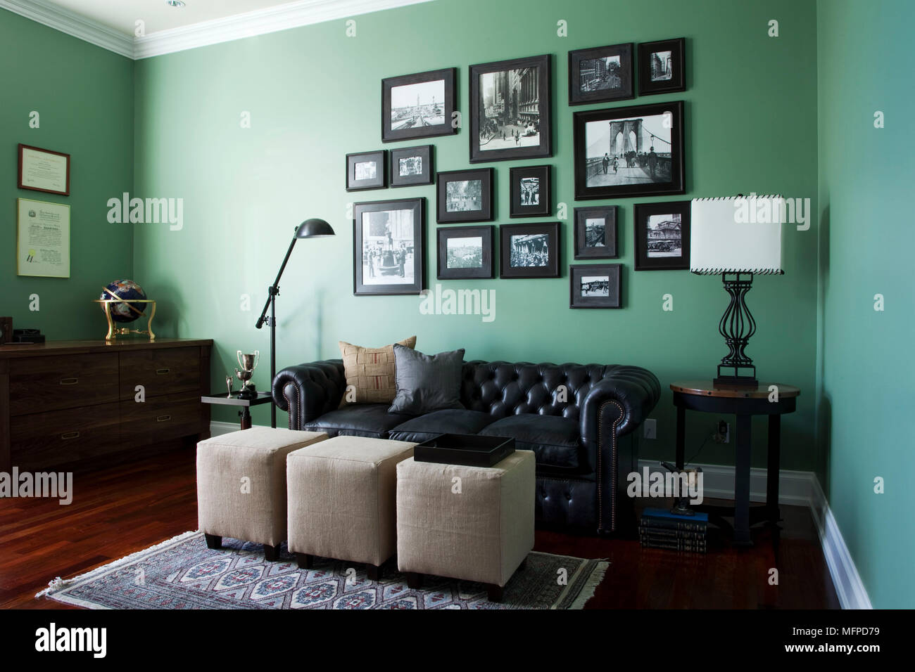 Arrangement Of Photographs Above Leather Chesterfield Sofa In Green