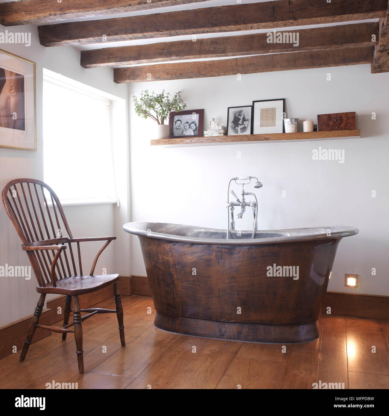 Freestanding Old Fashioned Bathtub In Centre Of Country Style Bathroom With  Period Chair