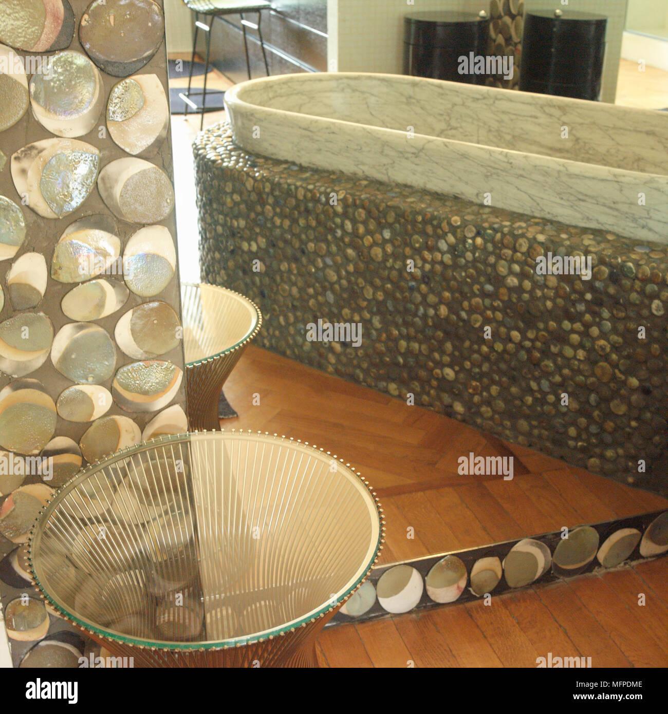 A modern bathroom, a marble bathtub set in a pebble and stone effect ...