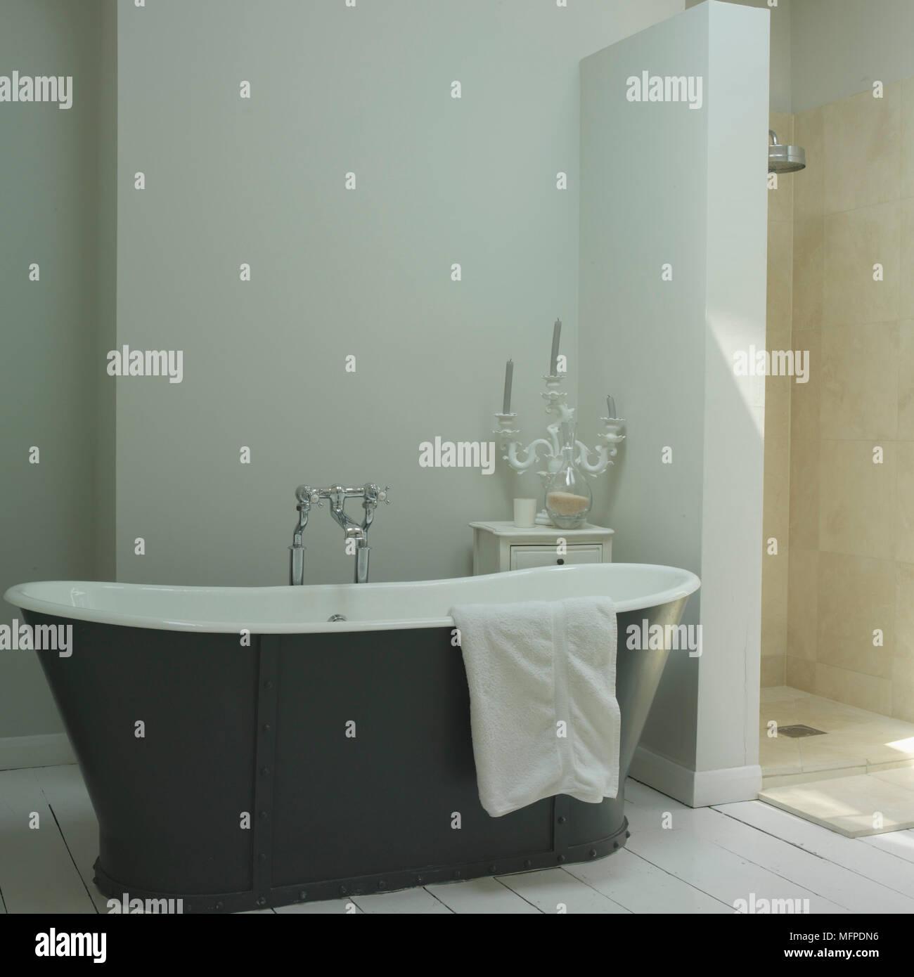A bathroom with a traditional style bathtub, shower unit, ornate ...