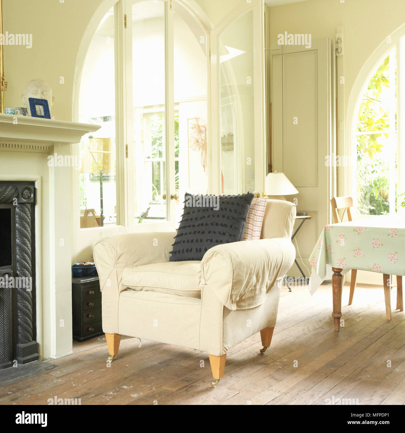 A traditional sitting room with an upholstered armchair next to a metal framed fireplace, open arched doors and a table behind. - Stock Image