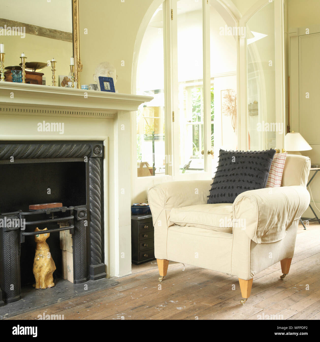 A traditional sitting room with an upholstered armchair next to a ...