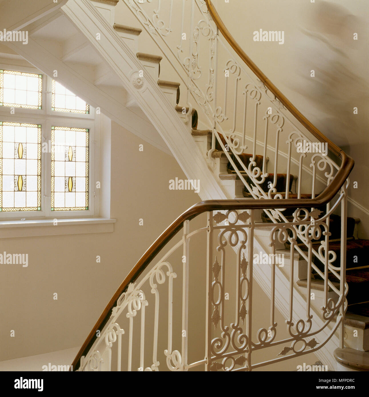 A Detail Of A Traditional Curving Staircase, Decorative Wrought Iron  Spindles, Stained Glass Window, Blurred Figure On Stairs