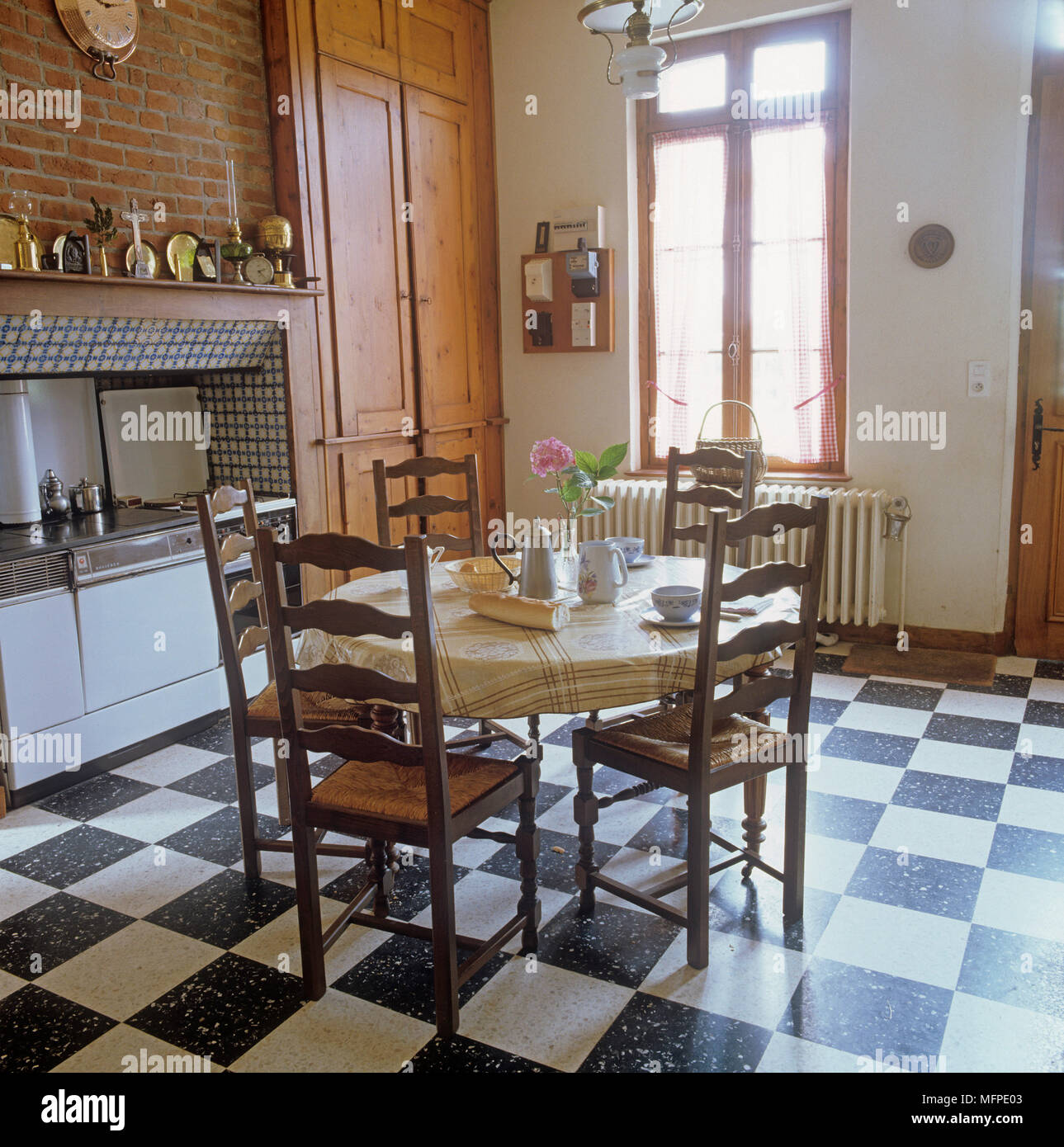 Round Dining Table And Wooden Chairs In Country Style Kitchen Stock